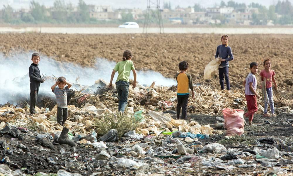 Flüchtlingskinder suchen im Müll nach Baumaterialien für ihre Hütten